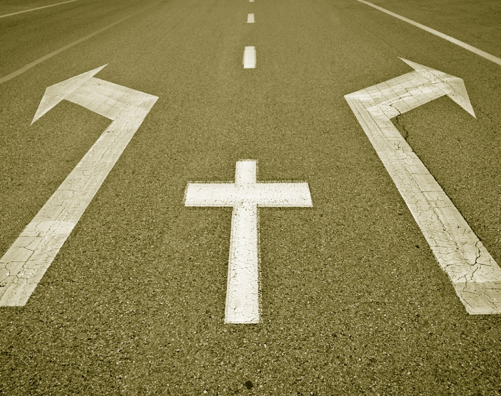 Road surface painted with a cross on the centre broken line and diverging arrows